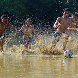 Playaing football on the mud field by Tamlikho Tam - Babies & Children Children Candids