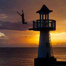 Lighthouse Leap by Patrick Tenny - Sports & Fitness Watersports ( jamaica, sunset, lighthouse, ocean, jump )