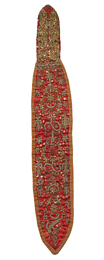 <b>Albanian woman's headband</b> Late 1800s or early 1900s  These long bands with stiffened tops were attached to the crown of the head and hung down to cover the plait at the back. The red cotton velvet band bears bird, crescent and sun motifs, executed in tiny metal coils and used in Muslim and Christian contexts.  To make the tiny metal coils, metal wire is wound round a thin rod to form a cylinder, which is then cut into pieces and the pieces sewn down, a technique known as purl work.