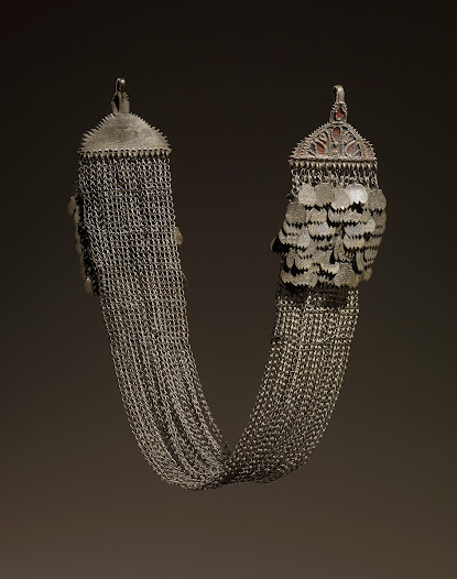 <b>Chain for headscarf (podbradnik)</b> Late 1800s  Head ornament or chin chain ('podbradnik'), silver alloy, formed of multiple chains ending in hemispherical plaques with a cluster of leaf-shaped pendants, cut out and stamped with ring and dot motifs.