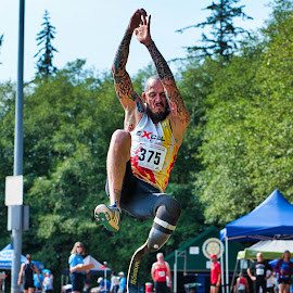 Going High In The Long Jump by Garry Dosa - Sports & Fitness Other Sports ( air borne, sports, jumping, athlete, track and field, people, summer, tattoo, long jump, outdoors, games, man, para athlete, male )