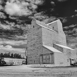Prairie Giant by Joe Chowaniec - Buildings & Architecture Decaying & Abandoned ( black and white, grain elevator, train, landscape, farming, abandoned )