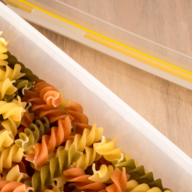 Fusilly in plastic container by Jacques Jacobsz - Food & Drink Ingredients ( old, italian, recipe, knead, diet, cultural, made, yellow, long, taste, heap, colour, dried, orange-red, tradition, glucose, three, cooking, gluten, tubes, fusilli, wheat, water, index, preparations, dry, green, colors, milled, pasta, prepare, table, boil, starch, many, history, soften, micro-nutrients, tasty, wooden, flour, semolina, food, staple, durum, culture, fibre, out )