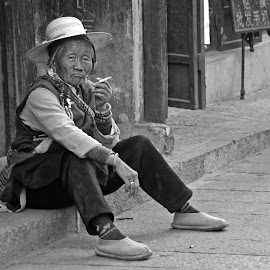 Chinese Lady by Barbara Neider - People Street & Candids ( traditional costume, cigarette, old, b&w, smoking, waiting, woman, tradition, original, dali, hat, china )
