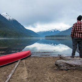 Birkenhead Lake View by James Wheeler - Landscapes Mountains & Hills ( calm, reflection, person, mountain, cap, canoe, beach, travel, landscape, hiking, caucasian, looking, tranquil, adventure, sky, nature, dramatic, alone, man, british columbia, water, sand, peaceful, canada, guy, majestic, male, rear, back, forest, lake, tourism, scenic, adult, overcast, relaxation, relaxing, boat, destination, resting, wilderness, birkenhead lake, red, wide angle, contemplation, outdoor, view, standing )