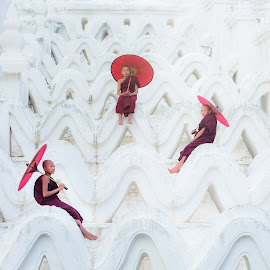 Asian young monk holding red umbrellas on the Mya Thein Tan Pagoda  by Nuttawut Uttamaharach - People Group/Corporate ( monk, pagoda, holding, buddhist, travel, architecture, bagan, stupa, people, kid, asian, child, religion, mandalay, buddhism, sky, spirituality, building, belief, white, traditional, tourism, young, buddha, temple, history, thein, landmark, two, myanmar, red, blue, outdoor, historical, mya, standing, religious, culture, tan )