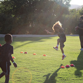 Kid jumping by Lauren Camargo - Sports & Fitness American and Canadian football ( football,  )