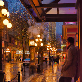 The Waiting Game by Garry Dosa - City,  Street & Park  Night ( rainy, waiting, streetscape, outdoors, wet, people, colours, city, weathered )