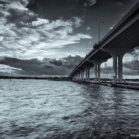 Storm Over Causeway by Fran Gallogly - Landscapes Weather ( clouds, jensen beach, stormy, ominous, monochrome, b&w, highway, black and white, waves, indianriver, pwcstorm, dusk, menacing, piers, florida, dark, cloudy, causeway, bridge, evening, cleary, river )