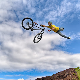 Flying Yellow Man by Marco Bertamé - Sports & Fitness Motorsports ( clouds, wheel, dow, yellow, stunt, helmet, bicycle, jump, flying, sky, blue, cloudy, man )