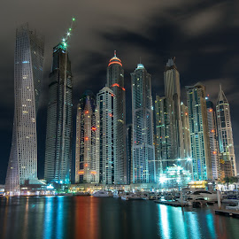 Dubai Marina at night in United Arab Emirates by Péter Mocsonoky - Buildings & Architecture Other Exteriors ( illuminated, arabic, emirates, skyline, arab, futuristic, architecture, cityscape, travel, middle, business, city, modern, lights, sky, skyscraper, dubai, buildings, marina, east, evening, downtown, water, office, building, united, sea, tourism, luxury, holiday, urban, landmark, tower, bay, contemporary, uae, popular, background, scene, night, view )