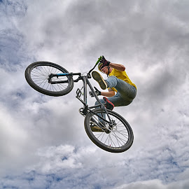 Fly High ! by Marco Bertamé - Sports & Fitness Other Sports ( clouds, wheel, from below, dow, yellow, stunt, bicycle, jump, two, flying, sky, blue, cloudy, grey, air, high )
