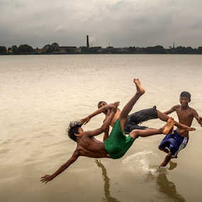 Playing in AIR by Debajit Bose - Babies & Children Children Candids ( children candid, monsoon, jumping, kids playing in river, kolkata, beautiful, street, children, kids playing, street scene, kids, street photography, jump, playing, kids candid, weather, 3 kids jumping, river )