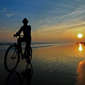 CYCLING ON THE BEACH by NEELANJAN BASU - Landscapes Beaches ( orange, cycle, blue, sunset, silhouette )
