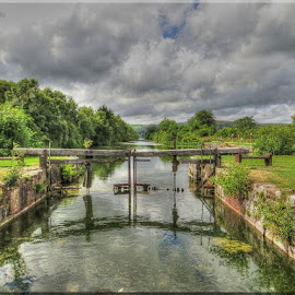 Storm Clouds over the Canal by Carol Lauderdale - Buildings & Architecture Bridges & Suspended Structures ( waterways, canals, stormy sky, reflections, dark clouds, ulverston )