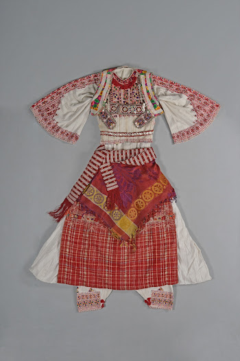This costume has two waistcoats. The front flaps are densely embroidered with glass beads and pearl buttons to protect against the evil eye. Although worn by Catholics, the solar patterns hark back to Pagan symbolism.