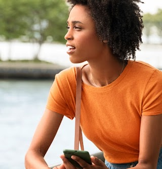 A woman in an orange shirt holding an Android phone.