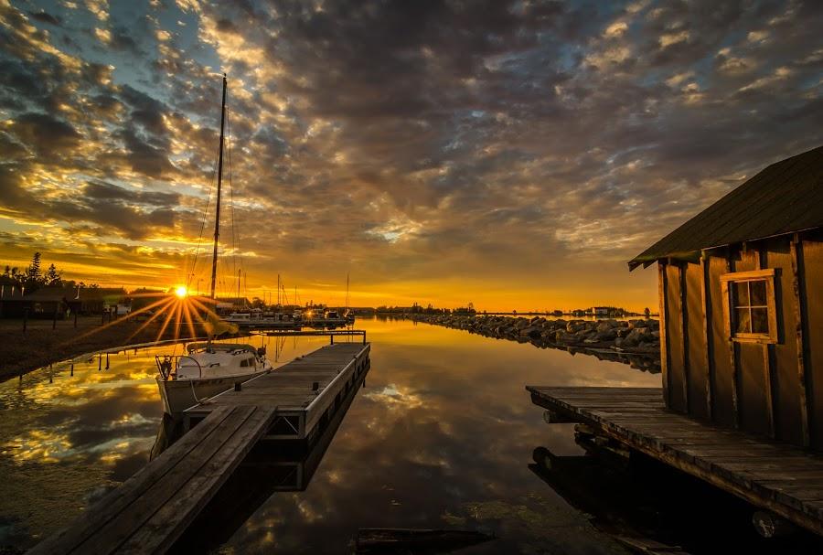 Marina Sunburst by David Johnson - Landscapes Sunsets & Sunrises ( clouds, sunburst, fish house, marina, sunrise )