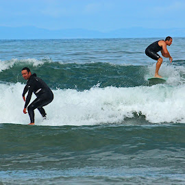 Two Guys Surfing by Jeannine Jones - Sports & Fitness Surfing