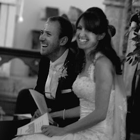 Laughter at the Alter by Martin Burnett - Wedding Bride & Groom ( church, black and white, vale, teeth, button hole, woman, dress, wedding, suite, bride, smile, laughter, groom, smiling, man )