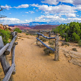 Arches Walkway by Ed & Cindy Esposito - Landscapes Deserts ( clouds, fence, monuments, desert, sky, arches national park, empty, rocks, alone )