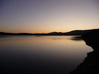 El atardecer permite ver el sol poniéndose tras las colinas que rodean el embalse