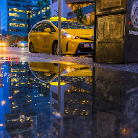 Yellow Cab in Two Dimensions by Steve Kazemir - Transportation Other ( puddle, vancouver, rain, bc, reflection, blue, cab, wet, taxi, yellow, water )