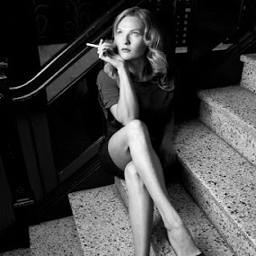 Adrienne by Leah Manzari - People Portraits of Women ( b/w, cigarette, blonde woman smoking, legs, film noir )