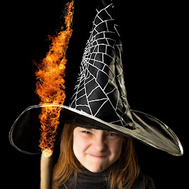 Funny little witch playing with fire by Mario Toth - Babies & Children Children Candids ( studio, expression, person, holding, little, people, kid, wand, hat, halloween, caucasian, flame, hand, child, girl, happy, witch, dark, childhood, celebrate, black, fun, young, portrait, fire, human, holiday, magic, female, dress, background, costume, small )