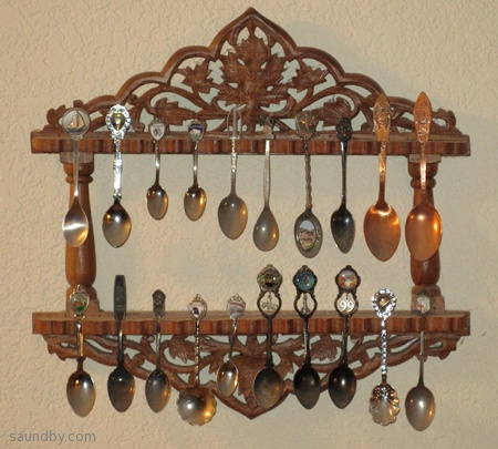 A pretty wooden rack for holding little silver spoons from around the world.