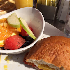 Gluten free roll with the egg sandwich from the menu. Included, bacon, cheddar cheese, and a fried egg. Side item was fruit salad.