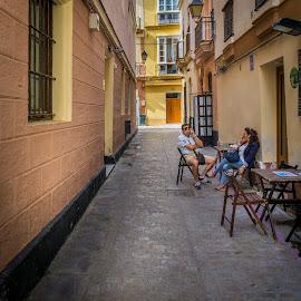 Alley in Cadiz by Ed & Cindy Esposito - City,  Street & Park  Neighborhoods ( cadiz, smoking, woman, street, cell phone, man, spain )