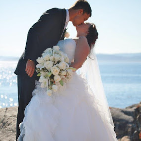 First kiss by Juli Paul - Wedding Bride & Groom ( sky, wedding day, wedding, beautiful, beach, bride, groom, rocks )