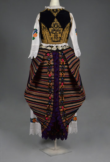 <b>Serbian Costume</b>  From the Sumadija, Central Serbia.   The hem is embroidered on the inside with stylised flowers and edged with purple cotton crochet in a scalloped pattern. The apron would be tied on inside out and arranged to reveal the embroidery. The bottom two corners are pulled up and tucked under the cord at the back to create a butterfly shape. The hem embroidery then hangs down vertically. The skirt is finally firmly secured with a decorative belt.