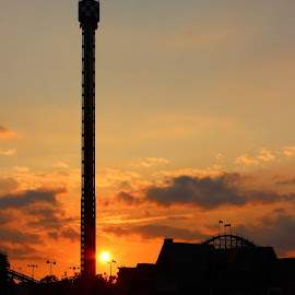 Fun In The Setting Sun by Reuben Nelson - City,  Street & Park  Amusement Parks ( setting sun, amusement park, orange glow, sunset, amusement parks, sun )