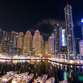 Dubai Marina at night in United Arab Emirates by Péter Mocsonoky - Buildings & Architecture Other Exteriors ( illuminated, arabic, emirates, skyline, arab, futuristic, yacht, travel, architecture, cityscape, middle, business, city, lights, modern, sky, skyscraper, dubai, buildings, marina, east, evening, downtown, office, water, united, building, sea, tourism, boat, luxury, holiday, landmark, urban, tower, bay, contemporary, popular, background, uae, scene, night, view )