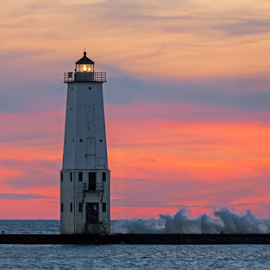 Frankfort Lighthouse Sundown by Kenneth Keifer - Buildings & Architecture Public & Historical ( reflection, setting sun, harbor, colorful, bright, shining, shine, glow, landscape, historic, sky, breakwater, long exposure, frankfort, frankfort lighthouse, surf, maritime, light, evening, clouds, waves, twilight, lighthouse, sea, horizon, seascape, great lakes, michigan, tower, red, lake michigan, splashing, navigation, sunset, lamp, sundown, night, beacon, breakers, nautical )
