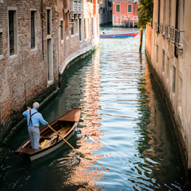 Man on a boat in Venice by Deyan Georgiev - Transportation Boats ( ride, famous, reflection, old, person, europe, italian, colorful, silhouette, travel, architecture, cityscape, transportation, people, cruise, historic, venetian, city, gondola, transport, grand, trip, place, italy, man, water, building, male, romantic, tourism, traditional, boat, canal, venezia, holiday, luxury, landmark, tourist, vacation, touristic, european, wooden, gondolier, venice, bridge )