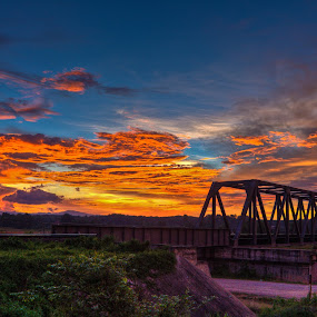 Cloudy skies by Ryan Dominguez - Backgrounds Nature ( red skies, train track, bridge under a red sky, sunset, cloudy skies )