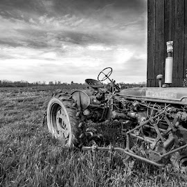 Kentucky Antique  by Jim Dawson - Black & White Landscapes ( tractor. farmall. barn. landscape. spring. history. weathered. )