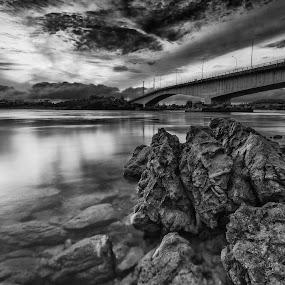 Under the bridge by Fariz Mohammad - Landscapes Cloud Formations ( clouds, reflection, monochrome, black and white, sunset, beach, bridge, sunrise, rocks )