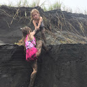 My daughter helping her friend at a black sand beach