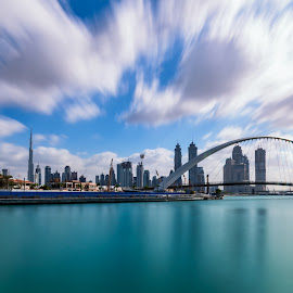 Dubai Skyline under the floating clouds by Shabbir Shani - City,  Street & Park  Skylines ( clouds, water, skyline, building, waterscape, tallest, nisi filters, skyscraper, dubai, floating, long exposure, bridge, nikon, waterfront )