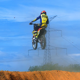 Ride On The Mast ? by Marco Bertamé - Sports & Fitness Motorsports ( electric, yellow, race, jump, mast, sky, motocross, blue, dust, clumps, air, alone, competition )