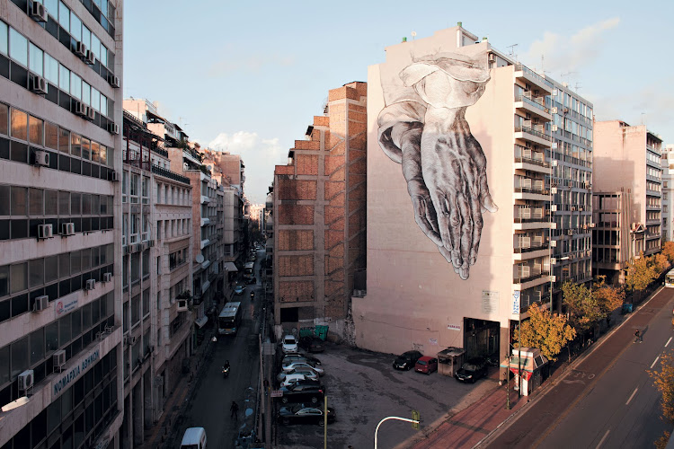 """At the height of the crisis in 2011, amid violent riots and the pinch of  austerity, students from Athens's art school painted their prayer for their city 11 storeys high. An inverted interpretation of German painter Albrecht Dürer's  16th-Century pen-and-ink sketch, the palms rest on each other, upside down on the road to the sea and the port of Piraeus. They called it, """"Praying for Us""""."""