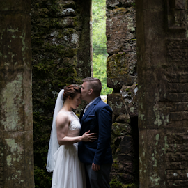 At Last by Charles Shope - Wedding Bride & Groom ( outdoor, green, castle, bride and groom, natural light, ballysaggartmore towers, wedding, ireland, stone )