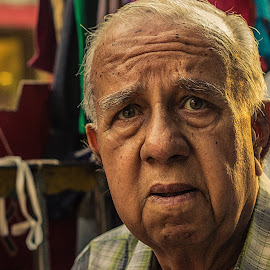 by Chittaranjan Bhat - People Portraits of Men ( curious, perplexed, street vendor, worried, tense, doubtful, astonishment, old man, eyes )