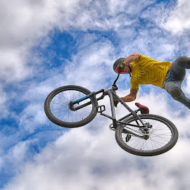 Yellow Bird by Marco Bertamé - Sports & Fitness Other Sports ( clouds, wheel, round, dow, circle, yellow, stunt, jump, bicycle, flying, sky, blue, cloudy, air, high,  )
