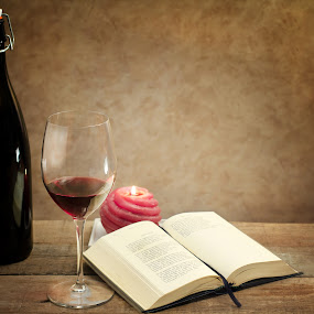 relaxing moment with wine glass and poetry book by Donatella Tandelli - News & Events Entertainment ( lecture, red wine, wood, aromatic, relax, romantic, candle flame, bottle, relaxing, poetru book, poetry book, transparency, candle, wine glass, lifestyle, tasting, book, glass, read, slow, novel, culture )