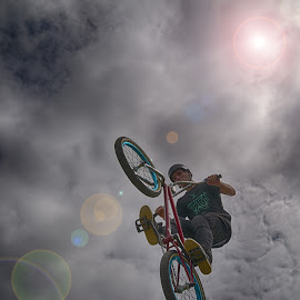 In The Sunlight by Marco Bertamé - Sports & Fitness Other Sports ( clouds, wheel, sunlight, stunt, sun, bicycle, jump, flying, two, circles, backlight, cloudy, grey, flare )